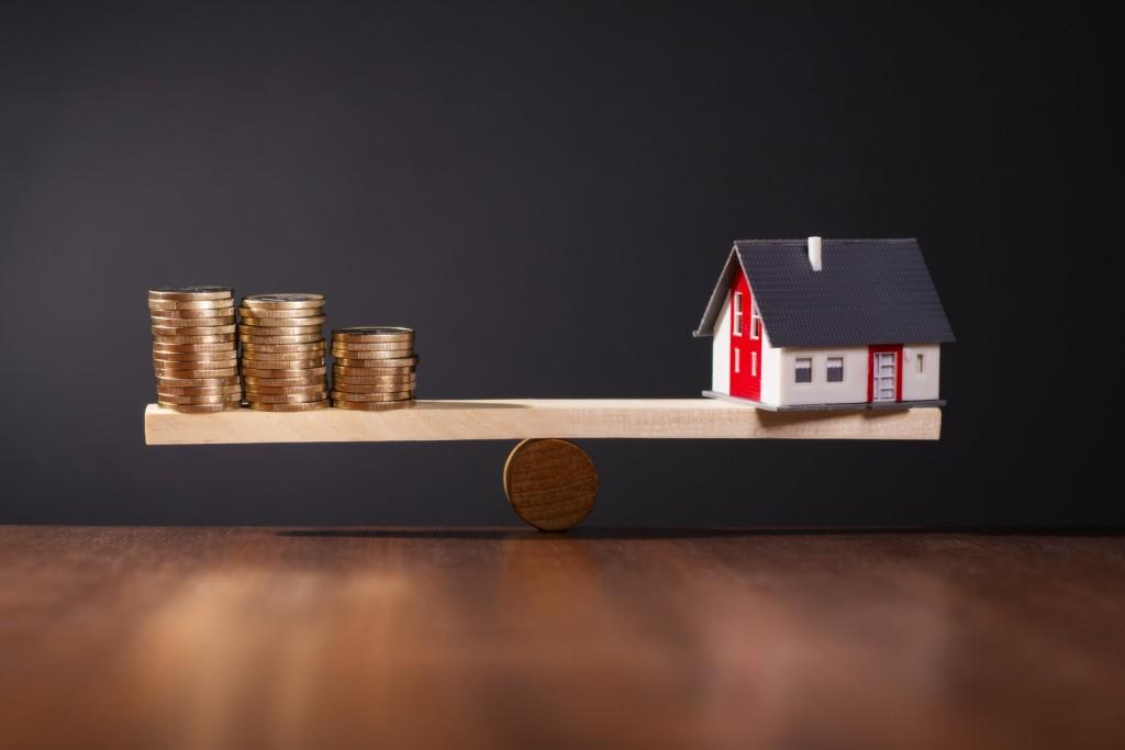 Wippe mit einem Haus auf der einen und Stapeln mit Münzen auf der anderen Seite.